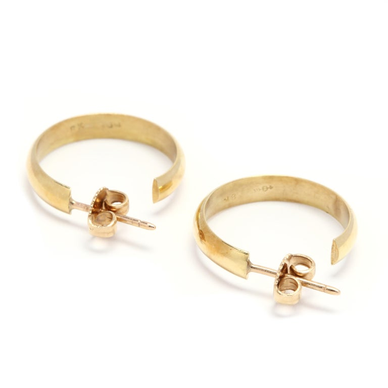 A pair of 18 karat yellow gold flat hoop earrings. These earrings feature a slightly curved polished hoop earring with push back closures.  Length: 3/4 in.  Width: 3.65 mm  3.49 dwts.  * Please note that this is a vintage item and may show signs of
