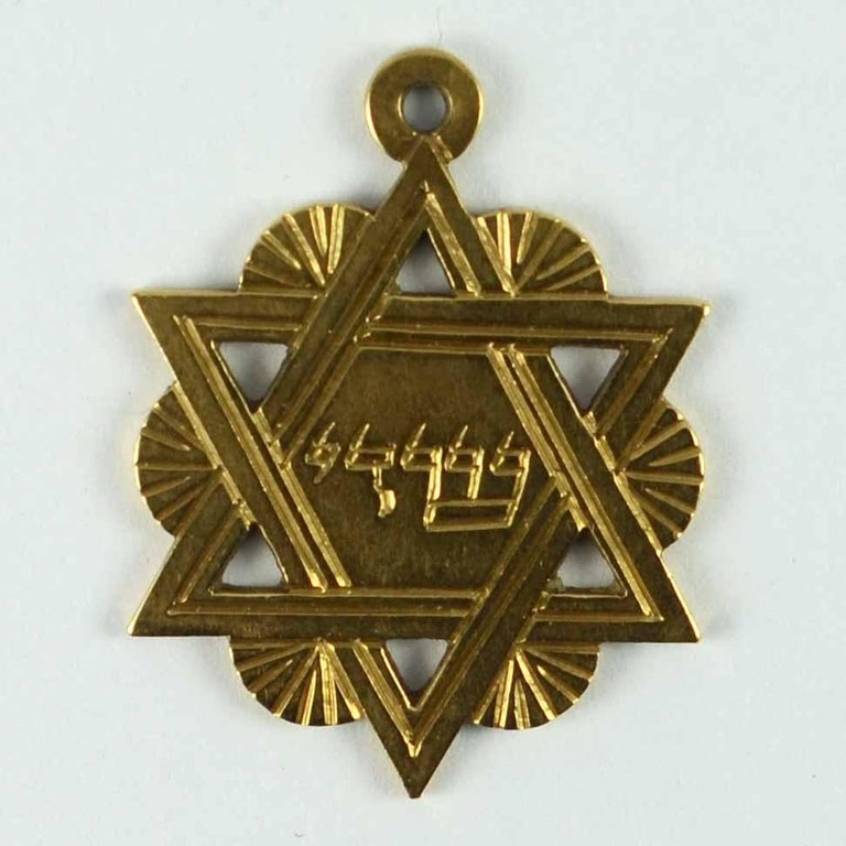A French 18 karat (18K) yellow gold charm pendant designed as the Jewish Star of David engraved with the Yiddish phrase for 'Shaddai', meaning 'Almighty'. Stamped with 750 for 18 karat gold to the reverse.  Dimensions: 2.8 x 2.1 x 0.1 cm Weight: