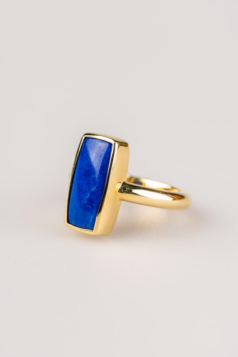 An 18k yellow gold ring set with a rectangle 7.7mm x 15.9mm  lapis lazuli cabochon, ring size 7. This ring was made and designed by llyn strong.