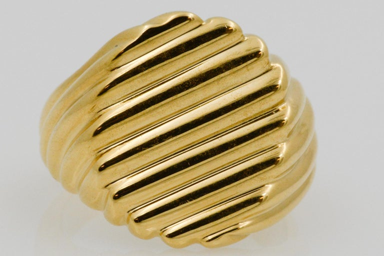 This 18k yellow gold men's ring has a flat face with a ridged design in a size nine. The ridges swirls around the edges and has a single design on the front.