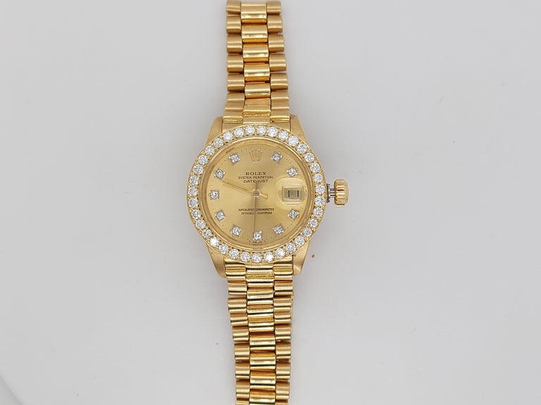 18Kt Yellow Gold, Rolex Ladies - Datejust President  Champagne Dial With Diamonds in Perfect condition.  Movement: Automatic  Functions: Hours, Minutes, Seconds, Magnified date window by the 3  Case: 18 kt yellow gold,  Diameter 26 mm, thickness