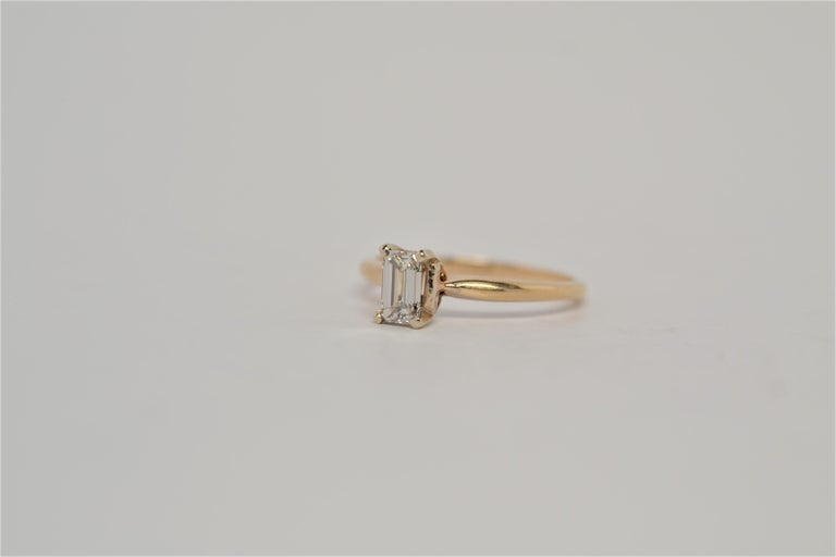 A traditional solitaire engagement ring with Emerald Cut Diamond center. The ring is made in 14K Yellow Gold with a four prong basket to set one diamond. The center is an Emerald Cut Diamond weighing approximately 0.50ct, diamond color grade range K
