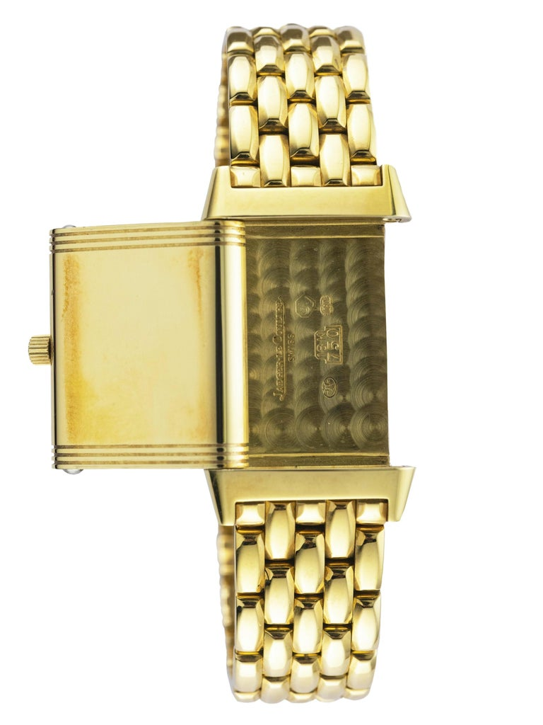 This yellow gold Reverso Watch has an argentè dial with blued steel hands. A yellow gold bracelet is accompanied by a double deployant clasp, also in yellow gold. The piece is fitted with sapphire glass and a manual winding movement. The watch is a