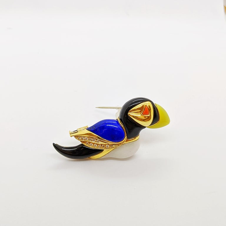 A true work of craftsmanship is the best way to describe this Puffin brooch. Smooth and hand polished stones of Jasper, Lemon Agate, Onyx, and Lapis  form the sculptural birds body. White round brilliant diamonds weighing 0.14 carats are set in the