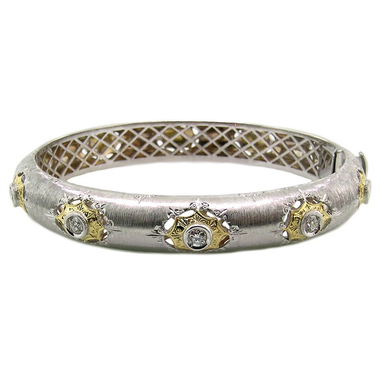 This two-tone 18 karat bangle is entirely finished in a richly detailed pattern which dates back to the Italian Renaissance. The execution and quality are old-world, but the style is both bold and feels very now; the sloped style is high