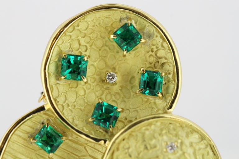18kt gold brooch with emeralds and diamonds. Fully hallmarked 18kt gold.  Approx Dimensions -  Size : 3.8 x 3.55 x 0.7 cm Weight : 16 grams  Emeralds -  Cut : Square Quantity : 7 Total Weight : 1.84 ct Origin : Colombia Treatment : Natural  Diamonds
