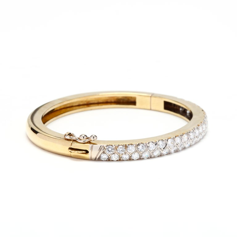 An 18 karat yellow gold diamond bangle. A hinged design with a double row of diamonds weighing approximately 3.5 total carats.  Stones: - diamonds, 44 stones - round brilliant cuts - 2.75 mm - approximately 3.5 total carats - F-G color, VS