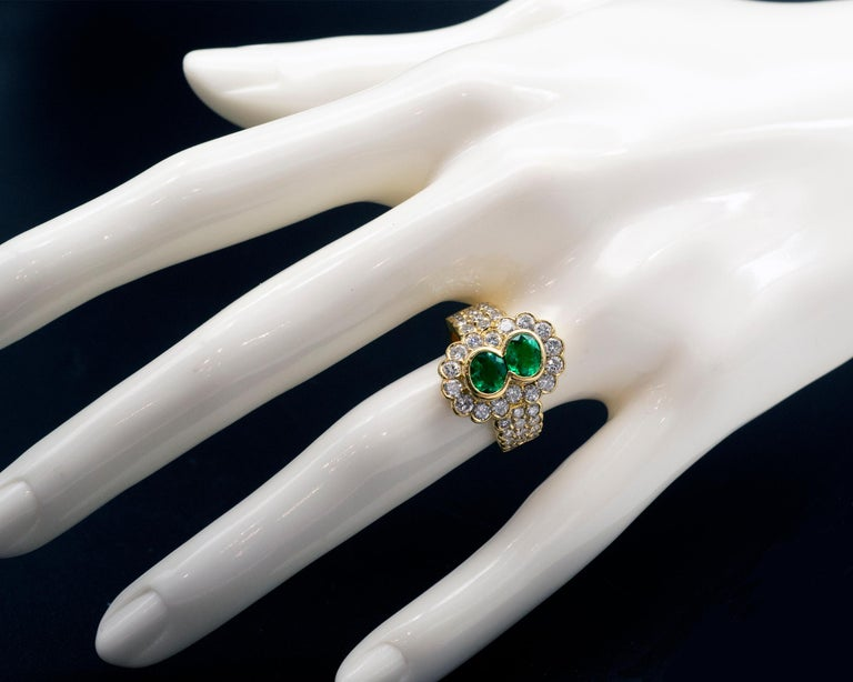 It is an opulent emerald ring showcasing two vibrant green oval emeralds. It is a one-of-a-kind halo ring with round brilliant cut diamonds skilfully set around the center gemstones as well as on the shaft. The whole ring is handmade in solid 18