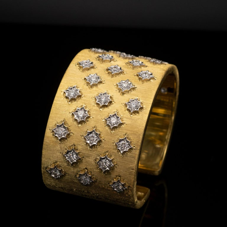 This beautiful large cuff bracelet is a perfect example of the florentine work style (style that has been made famous by Buccellati.) 33 white etched gold stars, inlaid in a fully engraved yellow gold body are set each with a diamond  A spring