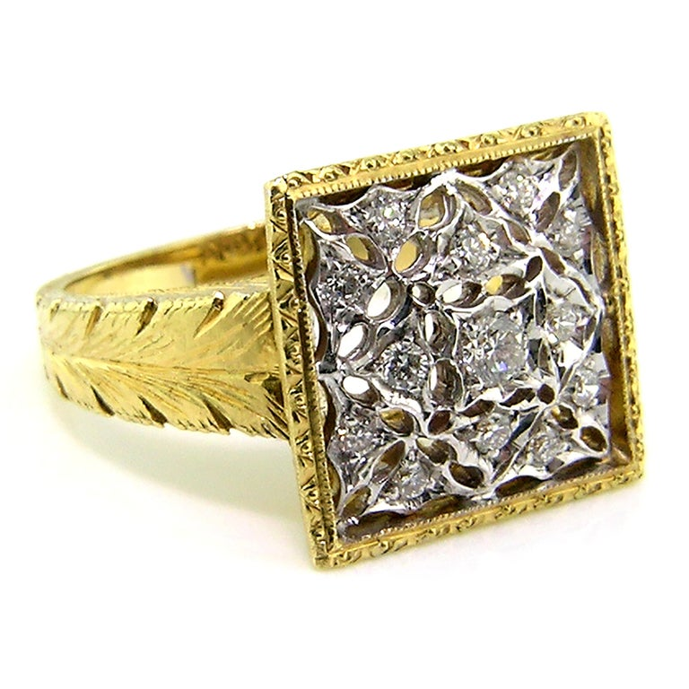 This statement ring is richly detailed all over with Florentine engraving, featuring a square crown of lace.  It is set with 0.30ct of fine quality diamonds, and it tapers to a comfortable fit underneath.  This ring measures approximately 14.5mm