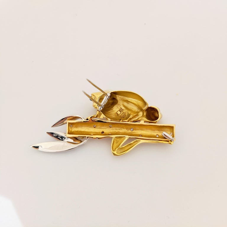 This lovely 18 karat gold brooch by Joell Prisma for Cellini Jewelers NYC, is designed with a hi-polished yellow gold frog with cabachon Emerald eyes. He is holding on to a Bamboo plant of rose gold, sprinkled with round brilliant Diamonds. The