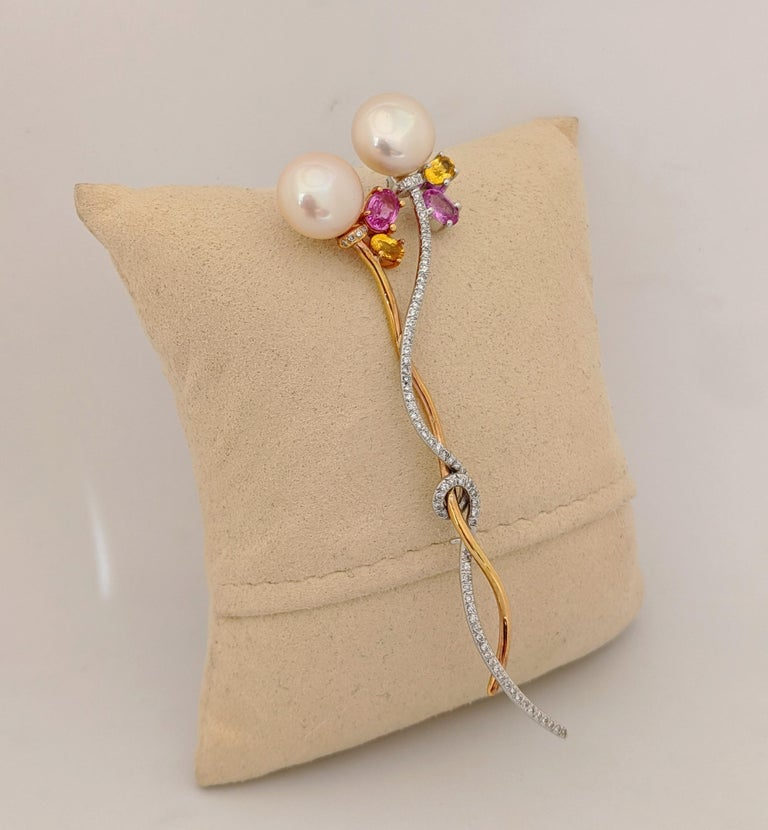A lovely brooch to adorn a lapel or dress,  This  brooch is designed with two freshwater pink pearls 11.2mm x 8.5mm.  Four Pink and Yellow oval shaped Sapphires are set under the pearls. The 18 karat white gold stem is set with round brilliant