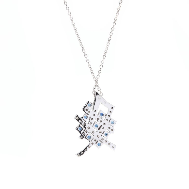 An 18 karat white gold, diamond and sapphire pendant necklace. Of a criss-cross design, set with round cut sapphires weighing approximately .40 total carats and round full cut diamonds weighing approximately .50 total carats and with a thin cable