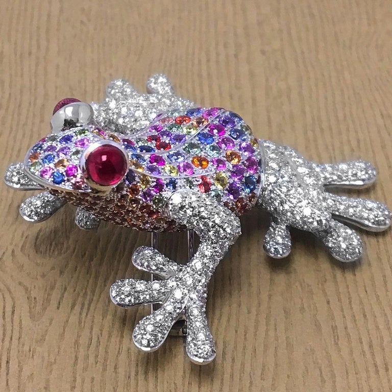 A frog is a good luck symbol in many cultures, also a symbol of fertility, transformation and safe travels. This adorable frog brooch is set with a pastel palette of multi colored Sapphires . His webbed arms and feet are set with round brilliant