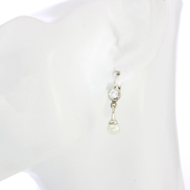 18kt white gold ladies clip-on earrings with cultured pearls and diamonds Made in the 1950s Tested positive for 18kt gold.  Dimensions -  Weight : 4 grams Size: 2.9 x 1 cm  Freshwater Cultured Pearls -  Approx weight each : 1 ct