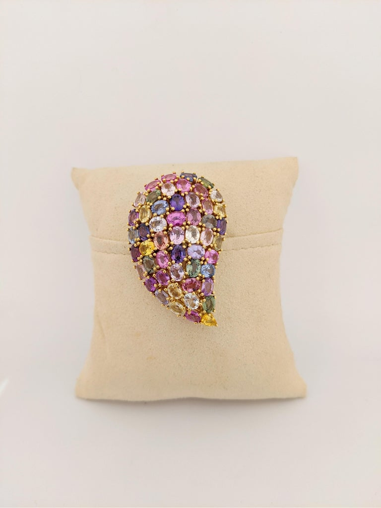 This lovely 18 kt yellow gold brooch is designed with an array of oval sapphires in vibrant colors. The paisley shaped brooch is easy to wear on a lapel or dress. The brooch measures 2