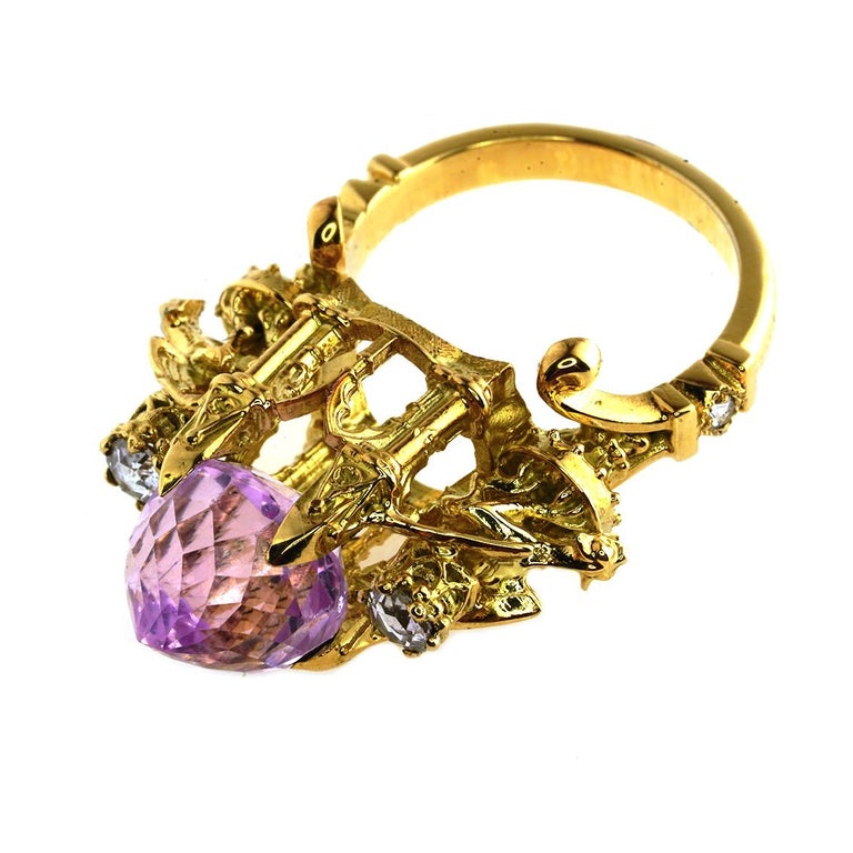 The Higher Divinity Ring is an exquisite piece. This incandescent ring is a one of a kind, luxurious masterpiece suitable for all divine entities  Handmade in 18kt yellow gold this incredible ring features a central, oval cut kunzite, claw set