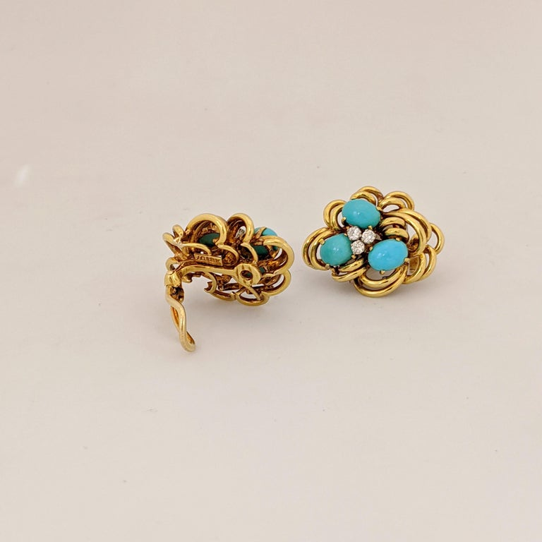 Beautiful 18 karat yellow gold cluster earrings centering three oval Turquoise stones, and three round brilliant cut  Diamonds in each earring. The earrings have a fold down post with a French clip back making them suitable for pierced and non