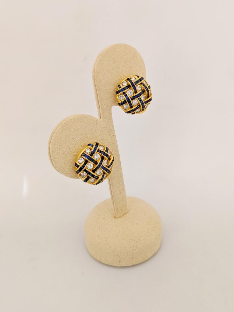 A Perfect Pair A pair of 18 karat yellow gold button earrings invisibly set with round brilliant Diamonds and square cut Blue Sapphires. The stones are meticulously set in a basket weave pattern. The earrings have a collapsible post and French back