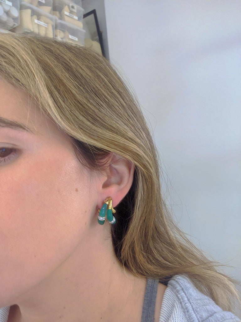 18 karat yellow gold earrings designed with two drop sections of carved Chrysoprase accented with round brilliant Diamonds. These earrings are clip on , but a post can be added. They measure 1