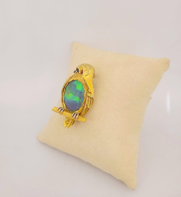 Designed as a King Puffin brooch. The artfully carved body is in 18 karat yellow gold with a sandblasted finish. The amazing feature is the birds belly which has been set with a large oval black opal . The opal has been set with the flat side facing