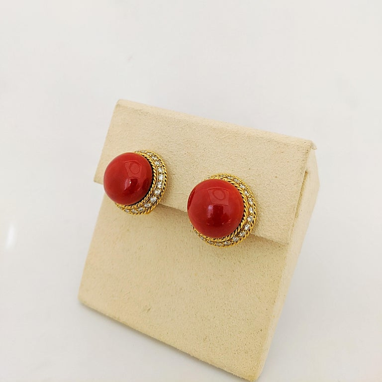 Very Rare,Very Retro  Amazing Oxblood Coral button earrings set in a beautiful 18 karat Yellow Gold setting. The rare and natural Coral gems are surrounded by Brilliant Cut Diamonds.  The Coral measures 16.5 mm. The earrings are clip on but can be