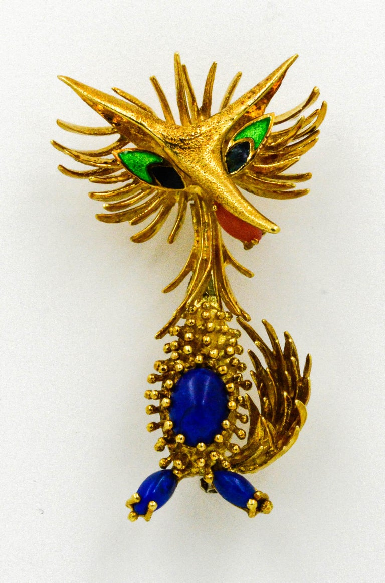 Circa 1945-1950 in a Retro style, we offer this stylized Toliro Animal. This roadrunner brooch is 18 karat yellow gold and set with 3 cabochon cut Lapiz Lazuli, 1 cabochon Coral, and accented with enameling.