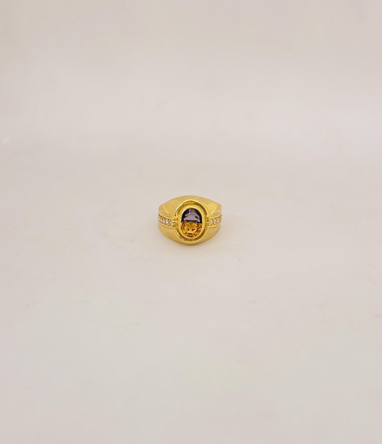 18KT Yellow Gold Ring centers a blue sapphire and citrine center - the stones are cut in a half moon shape forming an oval. The sides are flanked with 10 round brilliant diamonds totaling .26Ct. Blue Sapphire: .65Ct Citrine: .65Ct. Ring Size 7. 75