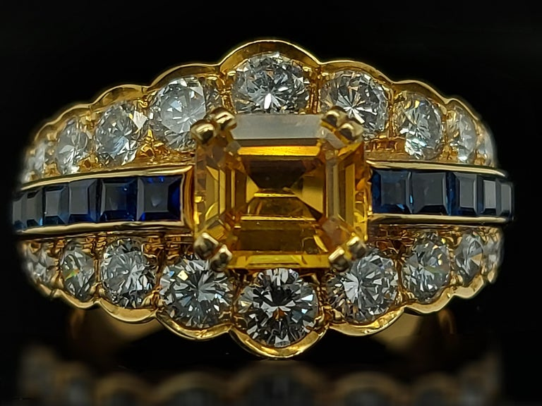 Magnificent 18kt Yellow Gold Ring With Large Yellow Sapphire, Blue Sapphires and Diamonds.  Sapphire: 12 small princess cut blue sapphires and large emerald cut yellow sapphire ca. 1.50 cts  Diamonds: 24 brilliant cut diamonds (together ca. 2
