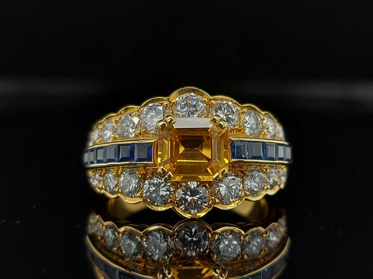 Emerald Cut 18 Karat Yellow Gold Ring with Large Yellow Sapphire Blue Sapphires and Diamonds For Sale