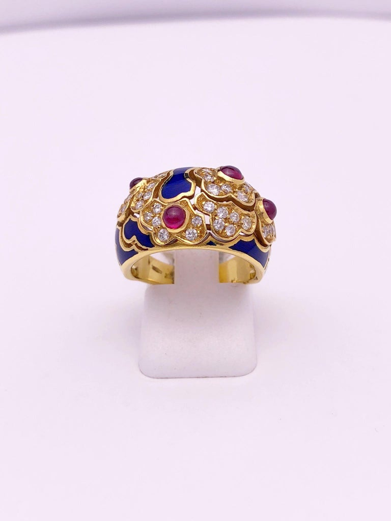 This lovely ring features a pattern of organic shaped flowers set with round brilliant diamonds. Each of the 4 flowers are set with a cabachone ruby. Blue enamel organic shapes finish off the ring which is entirely set in 18 karat yellow