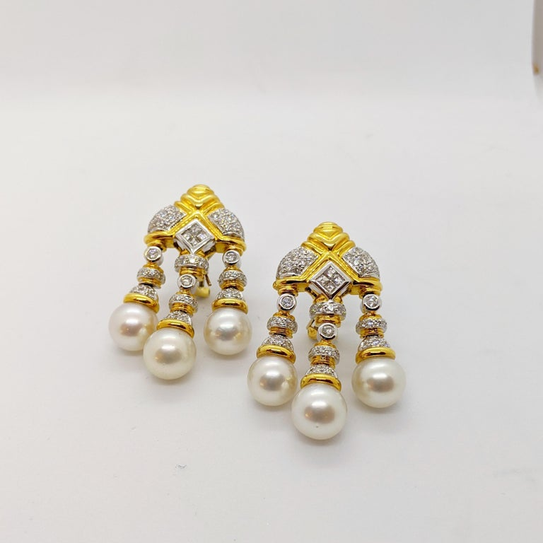 Queen for a day in these regal pearl and diamond drop earrings. The earrings are designed in 18 karat yellow and white gold . Each earring features 3 south sea pearls and a combination of round and emerald cut diamonds. The solitaire diamonds are