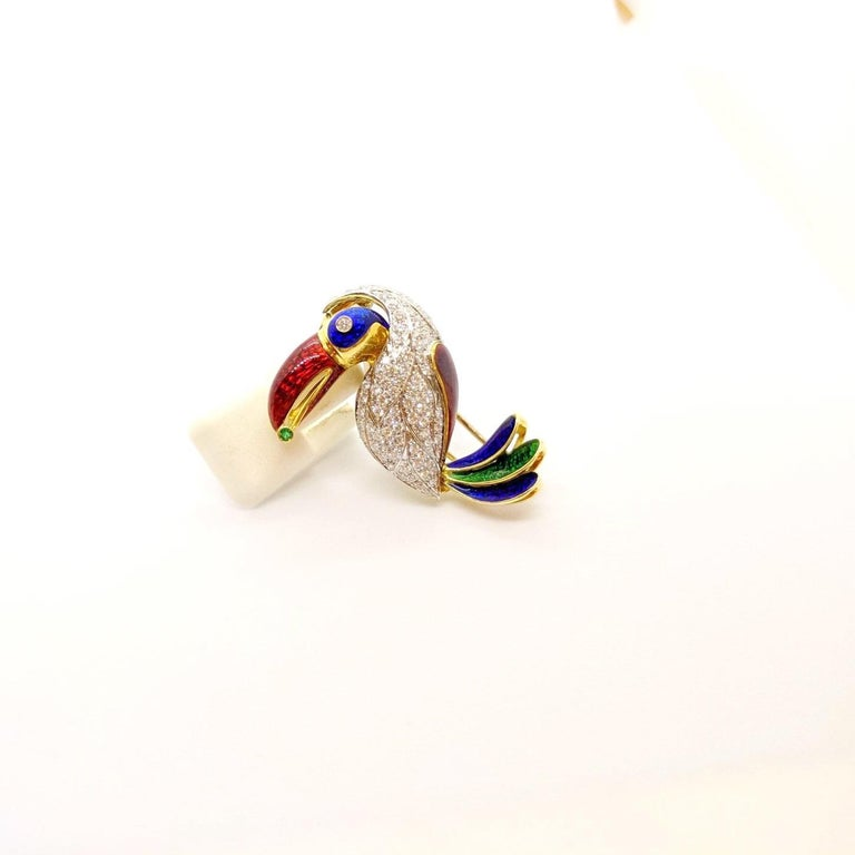 The absolute cutest Toucan. Set in 18 karat yellow and white gold, his feathers are set with round brilliant white diamonds. His eye , beak and tail feathers are crafted with guicholle enamel in red, blue, and green.  He has a bezel set diamond eye,