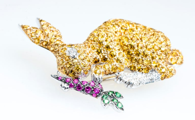 Vintage 18ky yellow sapphire, diamond, ruby and tsavorite bunny rabbit eating a carrot brooch/pin.   The rabbit body is made up of pave yellow sapphires and round diamonds for the eyes and feet.  The carrot is pave rubies and tsavorite for the green