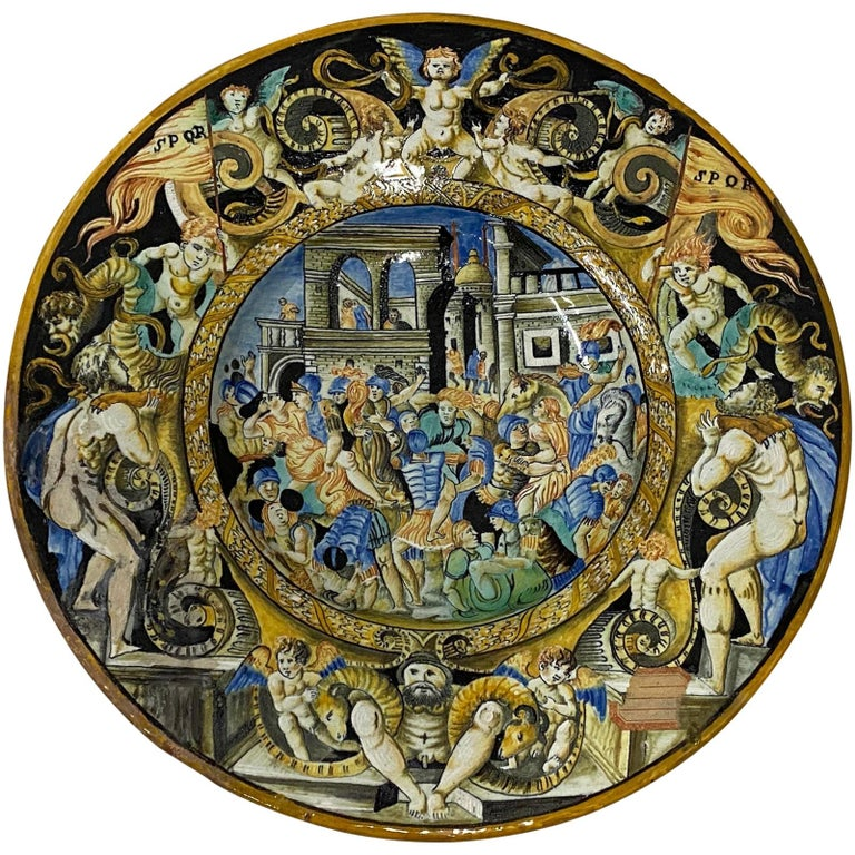18th-19th centuryItalian Istoriato dish with Renaissance figures  Superb highly decorated Italian Majolica plate with hand a hand painted scene of Roman mythology; The abduction of Sabine women. The border shows Classic Renaissance figures such