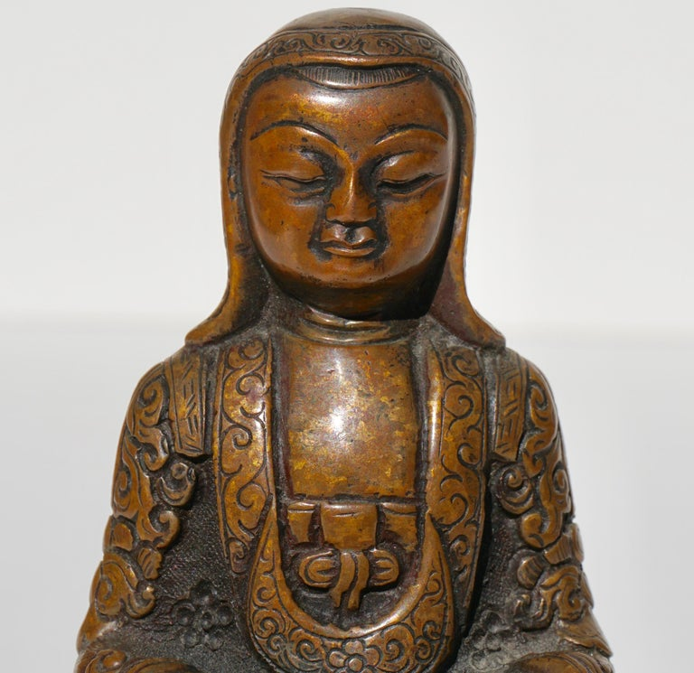 A peaceful Monk or Lama seated in a Buddhist crossed legged posture on a lotus throne (Padmasana) with both hands in a meditation gesture of Dhyana Mudra. His patched garments and bonnet are incised in a skilful manner typical of the Tsang atelier.