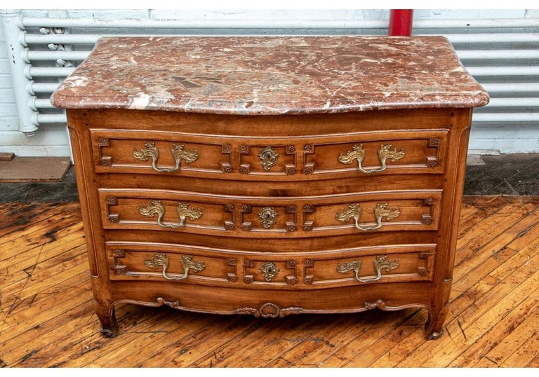 A shaped case with three long drawers carved with angular frames with rosettes. Each with new added compartments. Carved side panels, carved lower frame with leafy vines raised on carved shaped legs. With fine Baroque brass hardware. The drawers