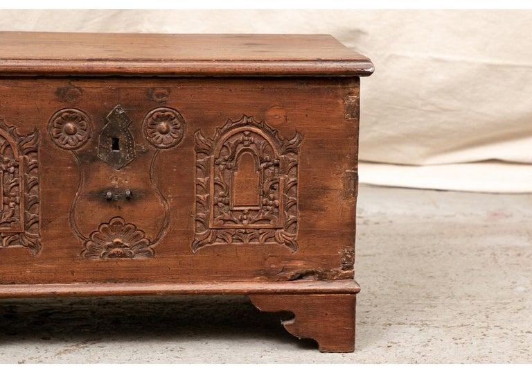 Carved panels on front - two arches with foliate frames and a shaped and scrolled one with rosettes in the center. The tin escutcheon lacks a key, and the lock lacks the bolt. There is a small side box in the interior.  Mortise and tenon