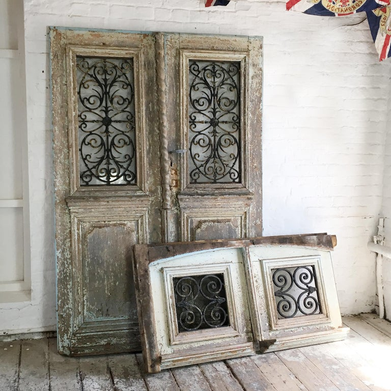 A pair of antique French oak chateau doors with transom, circa 18th century. Solid large exterior doors hand carved in oak with original transom. These doors and transom would have originally belonged to a French chateau the main doors have the