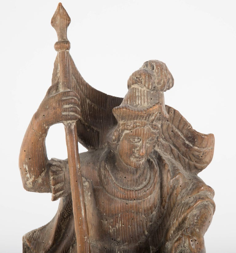 Pine carving of Saint Florian, the patron saint of fire fighters, 18th century German, the saint shown holding a staff with a banner in one hand, pouring a bucket of water over a burning bilding with the other. With an old label of Ludwig Roger, a