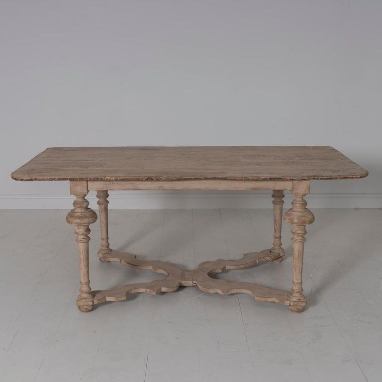 An 18th century Italian pine table on a 17th century base. This table is wearing a beautiful patina of natural aged pine and original paint.