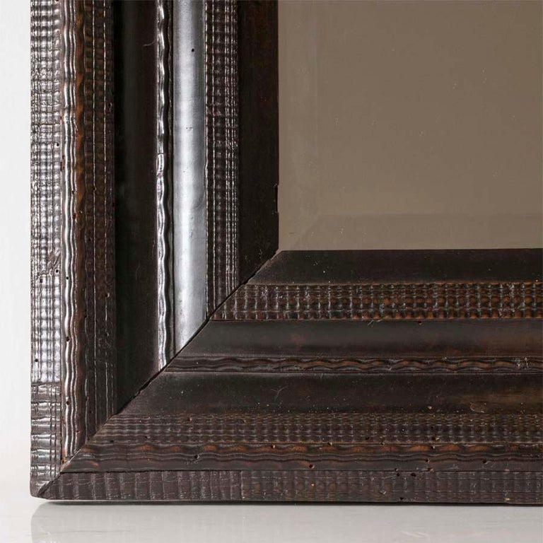 18th century Italian walnut ebonized mirror with finely carved guilloche detail. Measures: H 21.75, D 19.5, W 2.25 in.