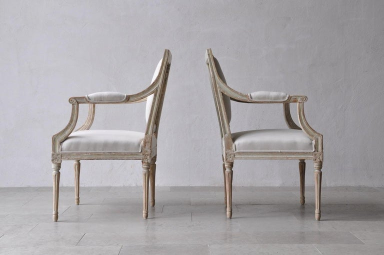A period pair of Stockholm made Gustavian armchairs in original paint. These beautiful chairs have been newly upholstered in new linen. Classic Gustavian chairs with lovely lean lines.