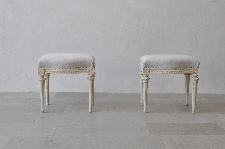 A beautiful pair of Swedish footstools from the Gustavian period signed by Melchior Lundberg (MLB), 1775-1812. These stools are wearing their original paint. There is carved egg and dart detail on the seat frame with rosettes on the corner posts.