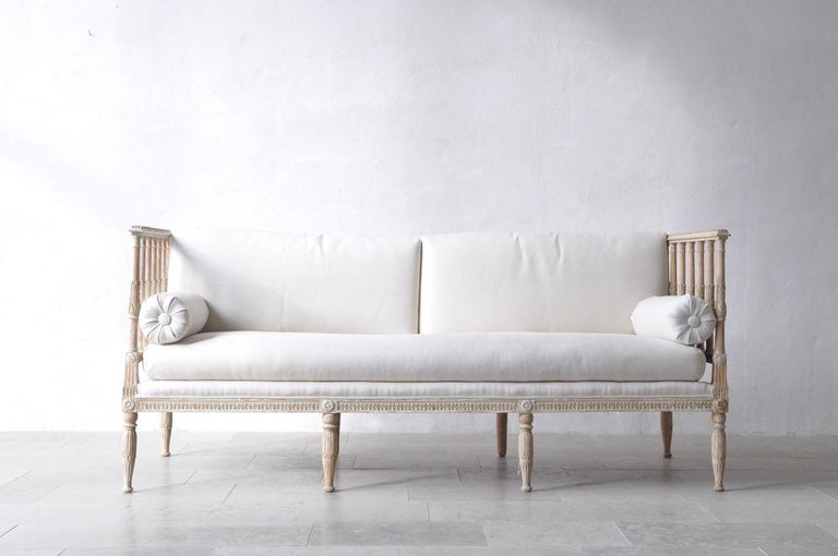An 18th century Swedish Gustavian period daybed made in Stockholm. This beautiful, circa 1790 daybed has been hand-scraped to reveal the original paint surface and newly upholstered in linen with side bolster pillows. Baluster sides with carved