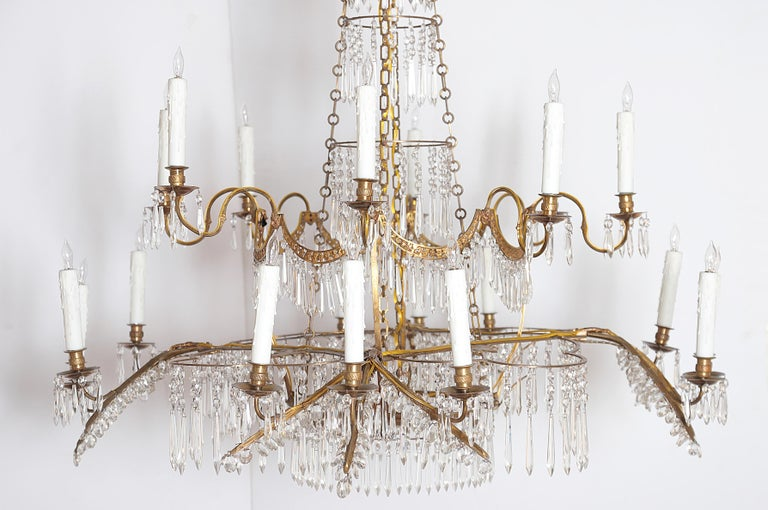 A German neoclassic ormolu and cut-glass twenty light chandelier, lower tier contains four (4) groups of three (3) lights or twelve (12) total, upper tier has two (2) branches for each of the four (4) groups below or eight (8) total, circa 1795,
