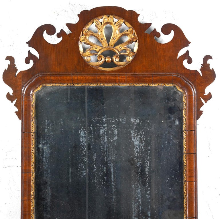 This fine English George II fret carved mirror dates to circa 1750 and features the original plate in a carved giltwood filet and a fret carved mahogany frame carved with ears and scrolls centering a circular pierced giltwood leaf in the crest and