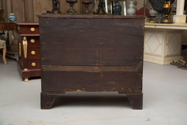 This is a fine and classic example of a solid mahogany 18th century American chest of drawers with incredible character. The rectangular top rests over four graduated drawers and raised on tall bracket feet, late 18th century.