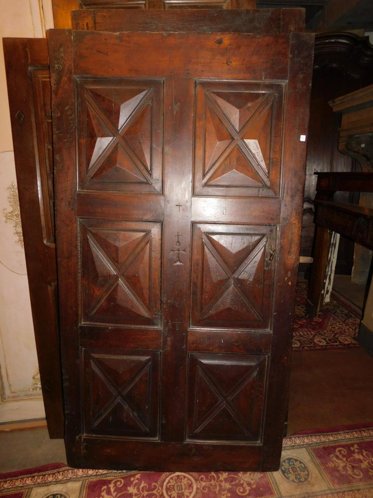 Antique brown walnut wood door, with hand carved cross symbols, 6 diamond panels, Italian north, entrance door with original irons, handle and hinges. Precious with high quality of wood and very old, it stands out elegance of the interiors.