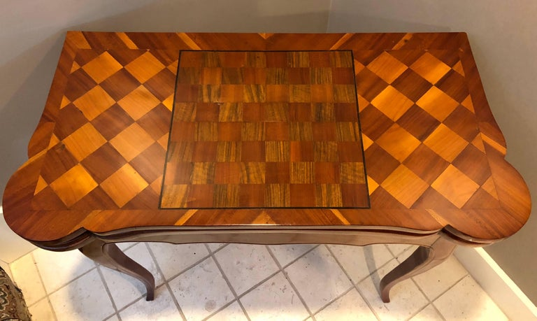 Stunning 18th century card table, South Germany, 1760. Cherry, elm and walnut veneer and marquetry. The outside of the top decorated with a chessboard. The opened table top is covered with green leather and has four compartments for poker chips. It